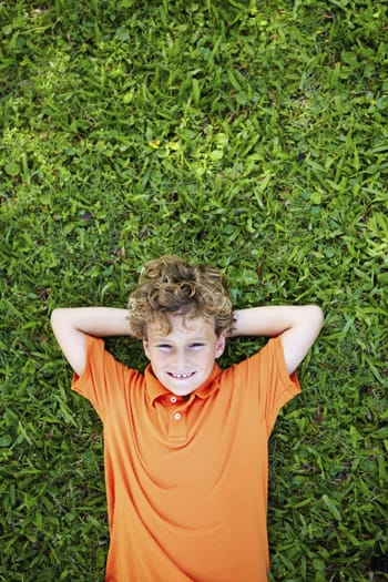 Boy reclining on the grass outside