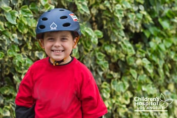 A young man displays how to correctly wear a bicycle helmet.