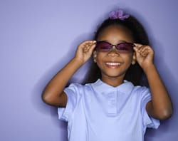 A smiling little girl sports a pair of purple sunglasses.