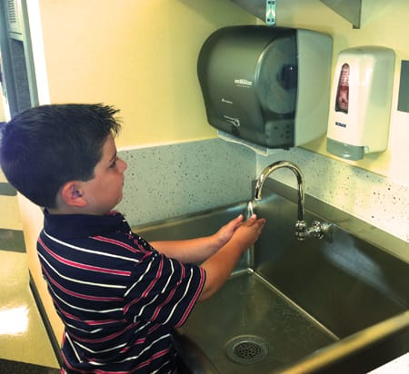 Boy washes his hands at a sink