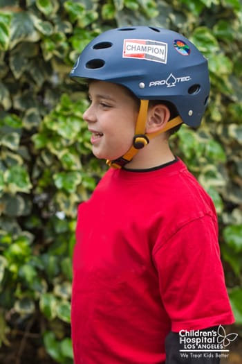 Boy demonstrates the proper position of a bicycle helmet when strapped.