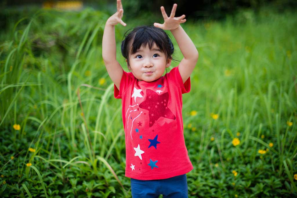 Young girl raising her hands above her head, outdoors in a grassy area
