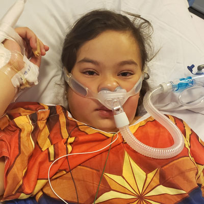 Xitlali laying in a hospital bed with a breathing device strapped to her nose