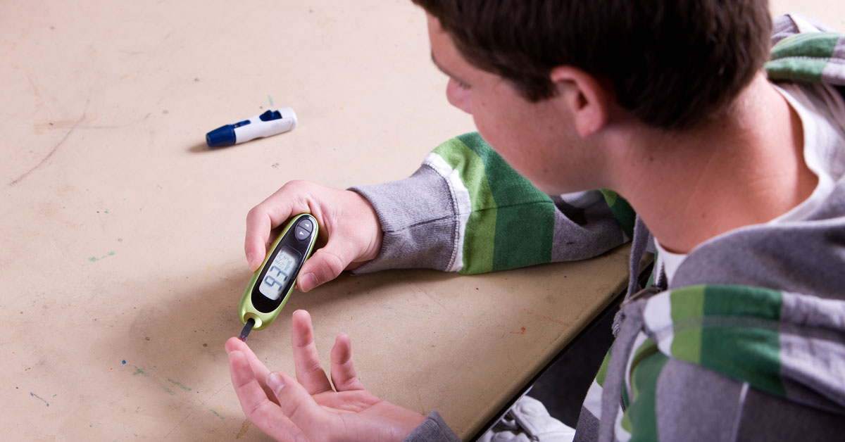 Teenage boy with type 2 diabetes performing a finger stick blood sugar test