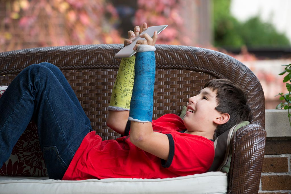 Boy with two arm casts laying on back and looking at ipad