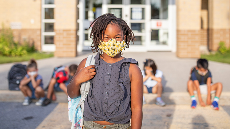Young girl wearing face mask in front of school