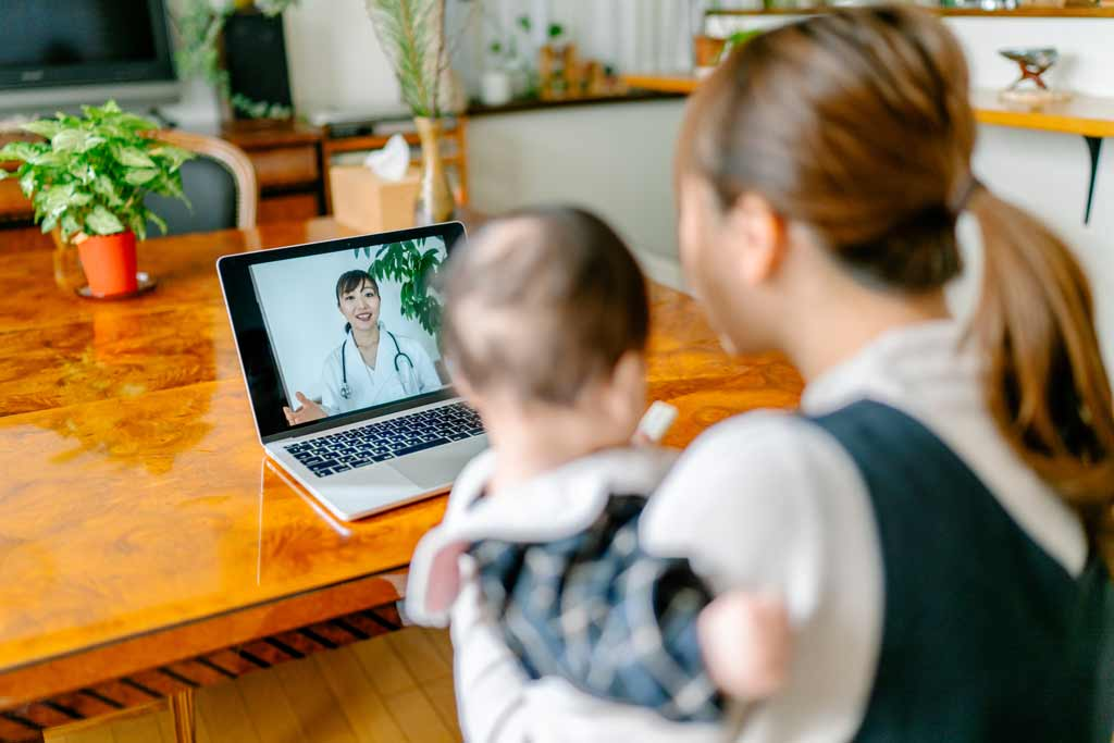 Mother and baby looking at laptop for a virtual appointment with doctor