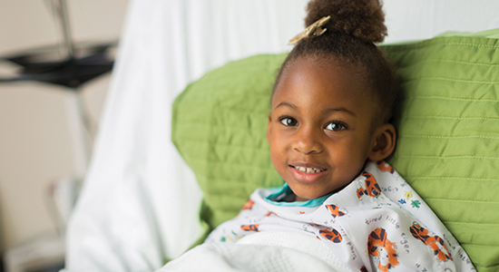 Young child smiling while laying on hospital bed - Coronavirus Safety at Children's Hospital Los Angeles