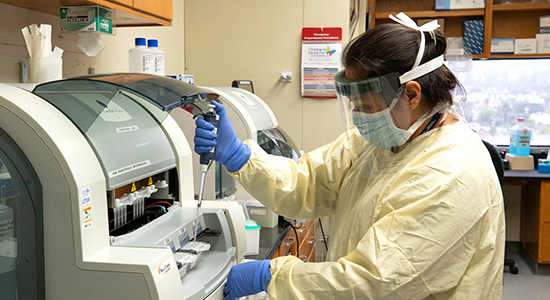 Woman wearing personal protective equipment testing samples at Children's Hospital Los Angeles