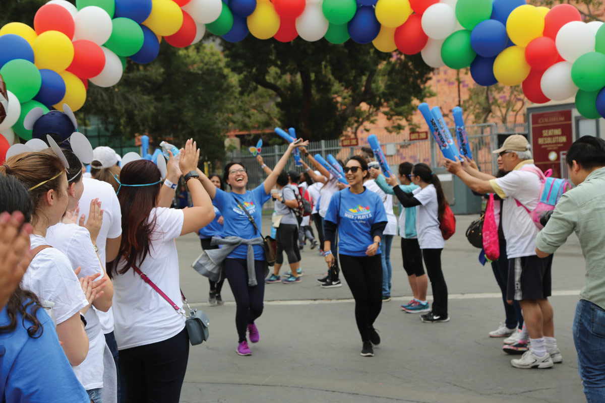 The enthusiastic crowd cheered as Disney VoluntEars (in blue) crossed the finish line.