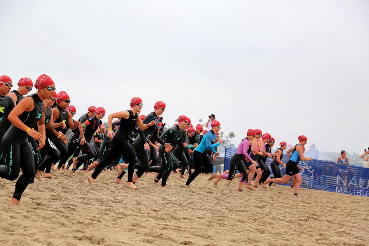 Participants race into the ocean for the ½-mile swim.