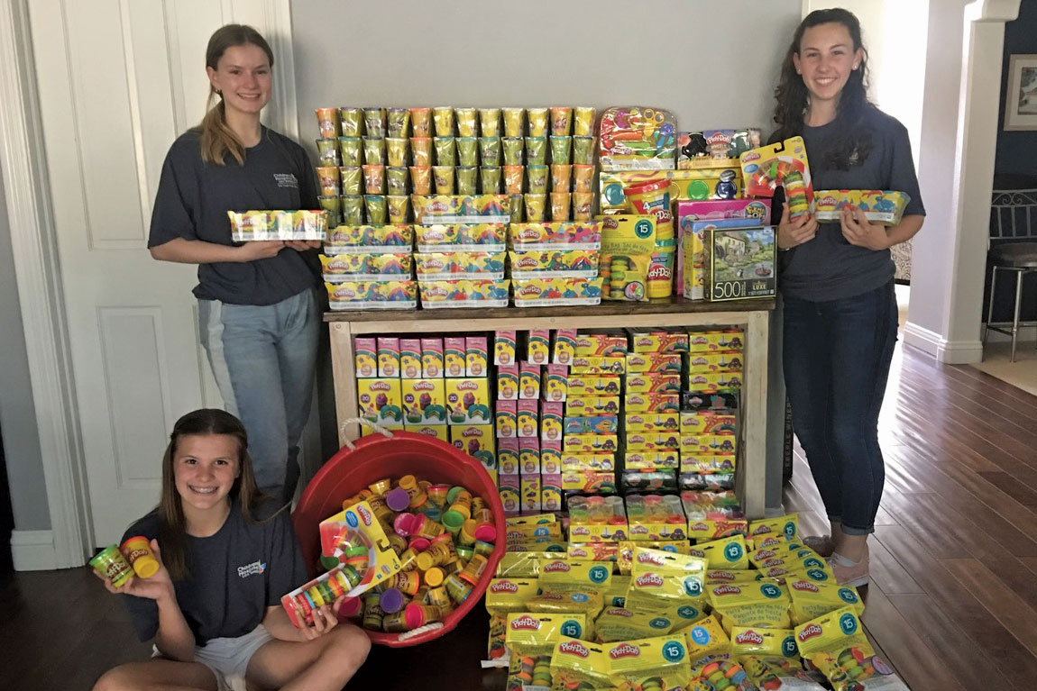 The Centennial Guild's Teen Group held a Play-Doh drive to help meet the CHLA Toy Room's high demand for the pliable substance. Left to right: Kennedy Youmans (seated), Jessica Baumann and Brenna Cheney pose with their group's efforts.