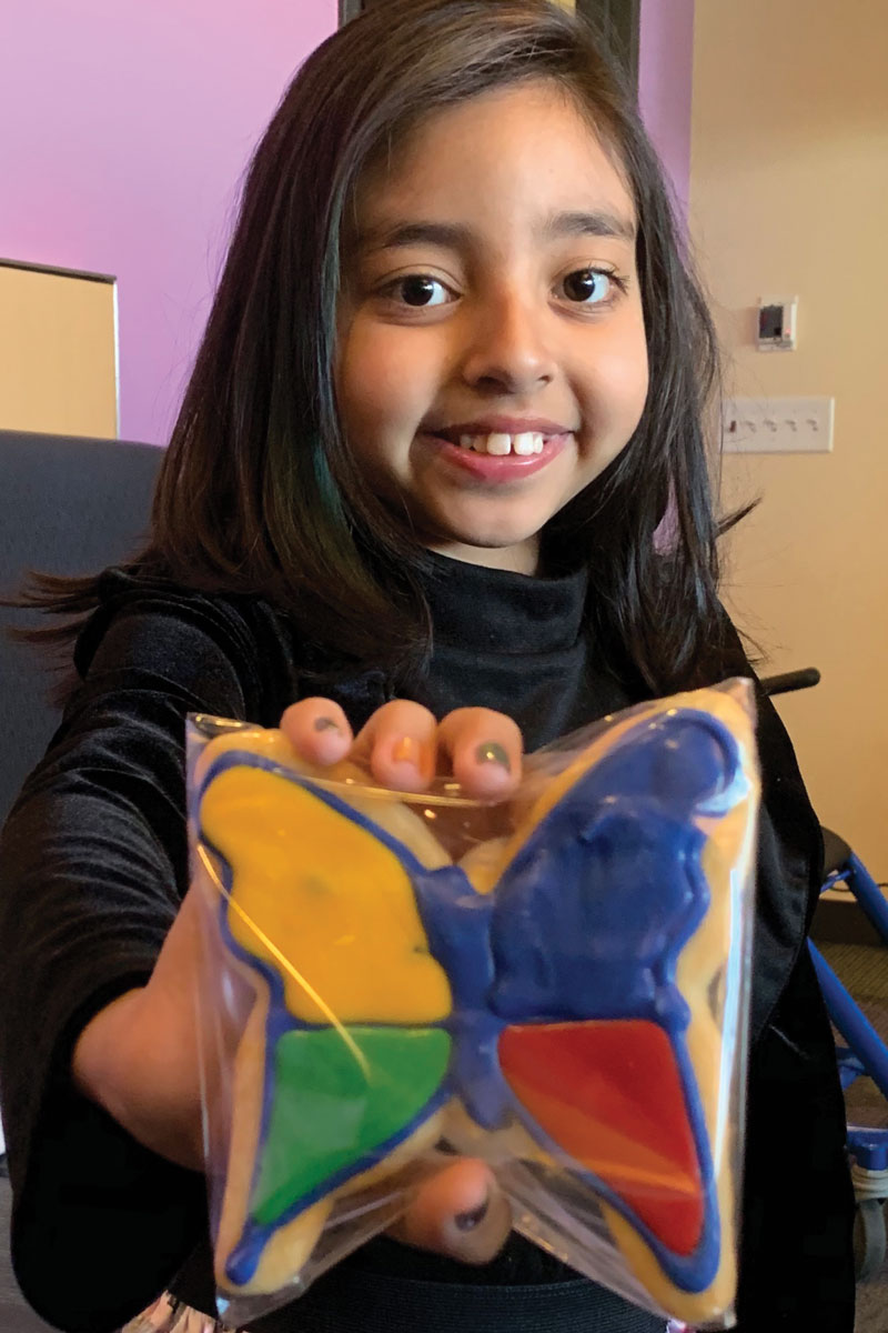 CHLA patient Kairi Ramirez holds a cookie created by Porto's Bakery in the shape of CHLA's butterfly logo.