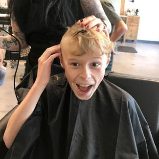 Malakai getting his head shaved at a salon