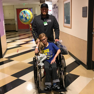 Malakai on a wheelchair being pushed by his father through the halls of CHLA
