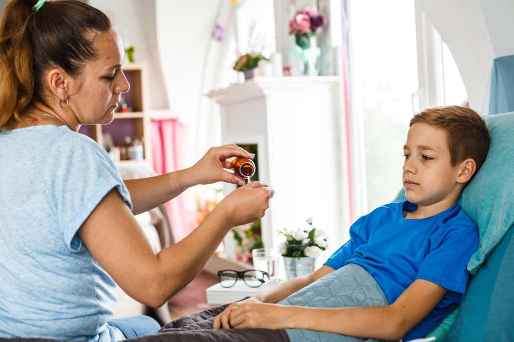 Mother giving liquid medication to son