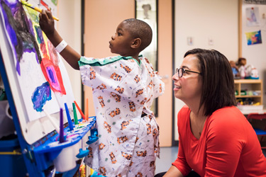Child Life specialist with a young patient painting