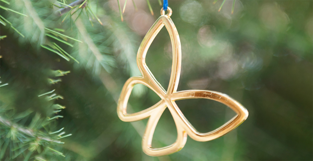 Close-up of a gold CHLA butterfly ornament hanging from a Christmas tree